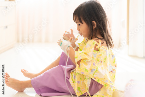 Photo A cute 3 years old girl is drinking the water in the hospital room when she admi