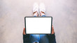 Top view mockup image of a woman holding black tablet pc with blank white screen while sitting on the floor