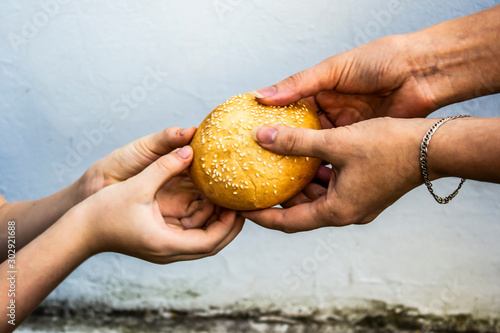 Hands of a child take a bun from the hands of an adult Canvas Print