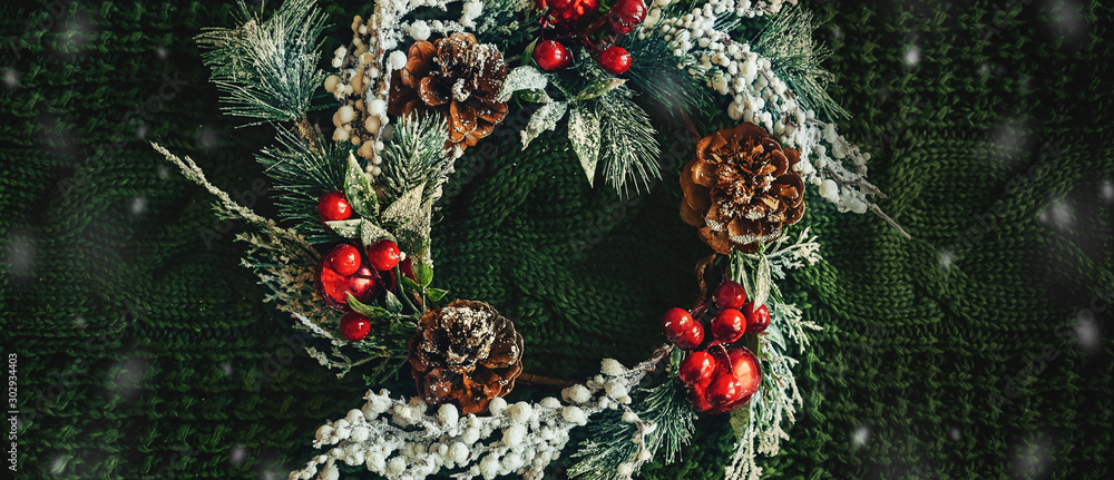 Fototapeta Pine wreath and Christmas decor on a green knitted background. Flat lay, elegant style. Christmas, New Year, preparation for holiday Banner