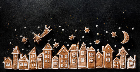Christmas background, gingerbread  cookies houses and gingerbread stars  on a black  background. Christmas gingerbread town