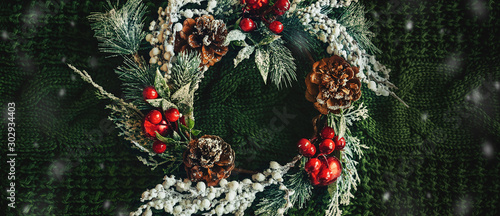 Pine wreath and Christmas decor on a green knitted background Fototapet