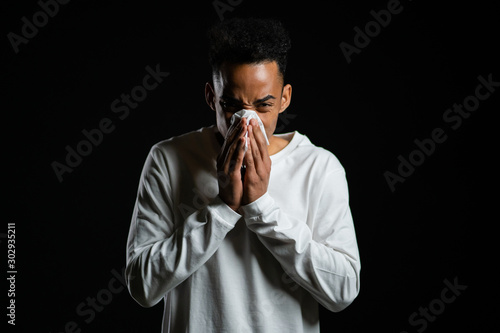Valokuva  Young african american man sneezes into tissue