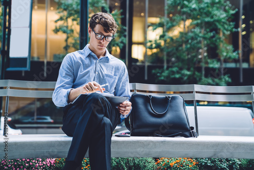 Thoughtful male using tablet sitting on bench