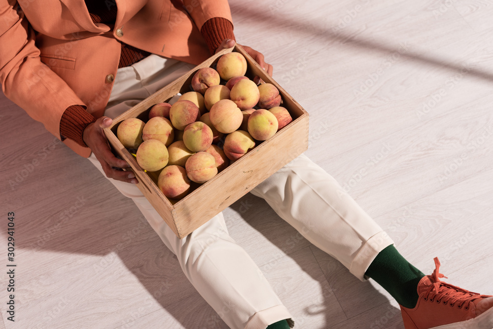 Fototapeta cropped view of man in blazer sitting with sweet peaches in box on white with shadows