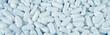 Leinwandbild Motiv White pills spilled on blue wooden background