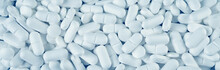 White Pills Spilled On Blue Wooden Background