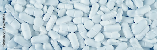 Fotografia White pills spilled on blue wooden background