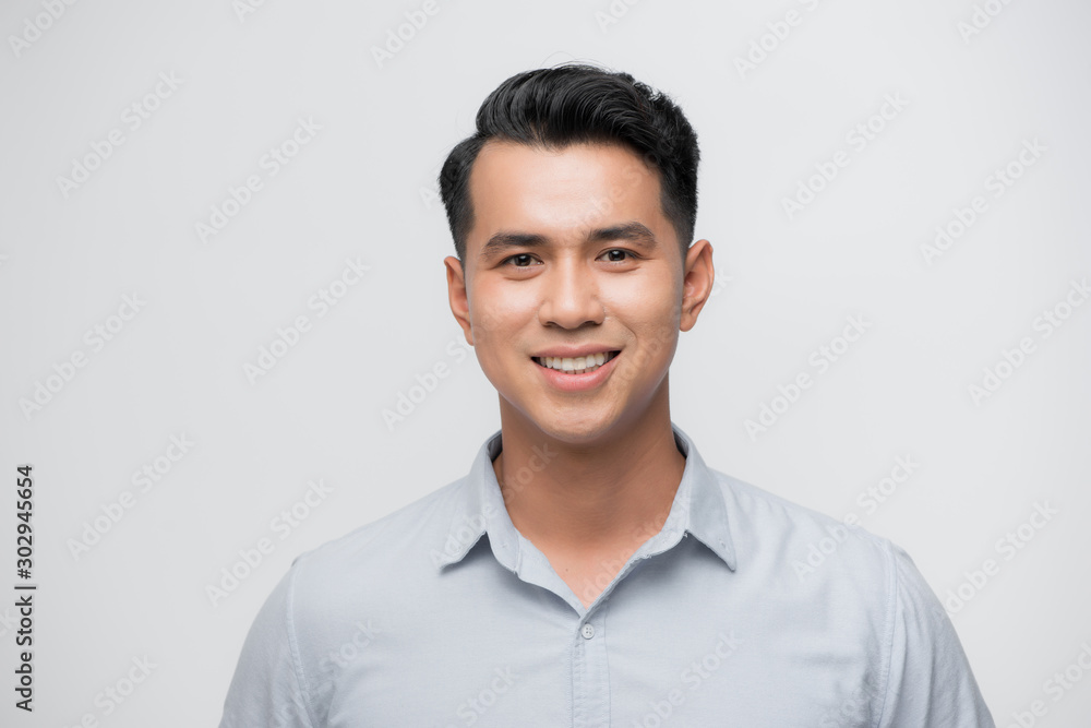 Fototapeta Young good looking asian business man on a white background isolated