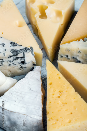 Fotomural different varieties of cheese, hard, brine, soft and with mold on the table