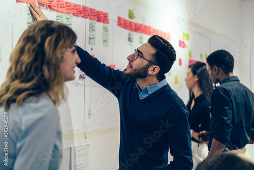 Fototapety, obrazy: Group of young multicultural perspective managers creating idea of strategy for productive work of company, curiosity male expert in optical spectacles reading interesting note from sticks on wall