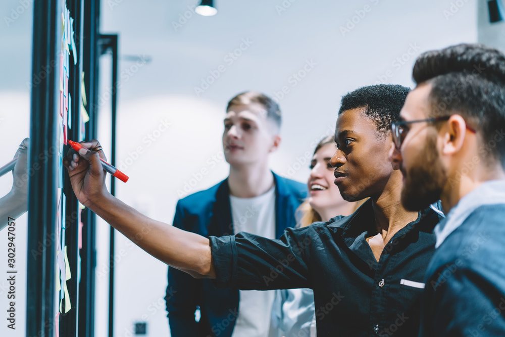 Fototapeta Group of diverse employees concentrated on idea during meeting in office, African American men worker in formal wear writing information on sticky note while brainstorming together with colleagues