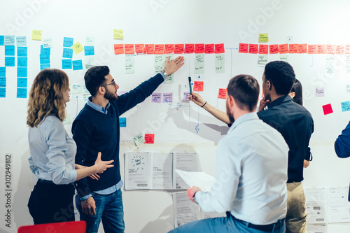 Fototapety, obrazy: Intelligent male professional pointing on colorful stickers with text message glueded on wall and discussing information with creative multicultural colleagues having brainstorming meeting in office