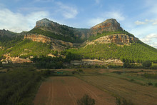 Panorama View On Empty Farmers Fields In Front Of Green Overgrown Flat-top Mount / Table Top Mountain In The South Of Spain North Of The Sierra De Andújar At Beautiful Weather With Blue Sky