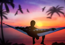 A Men Relaxing In Hammock At Paradise Island With Birds Flying Or Dreamy Evening On Sunset Beach.