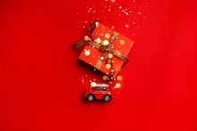 Minimal Creative Holiday And Travel Composition Of Red Toy Car Toy With A Gift On The Trunk, Blurry Glitter On A Red Background
