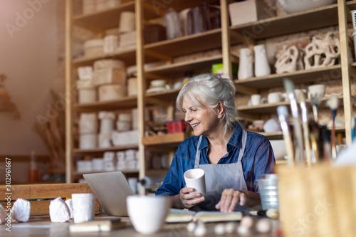 Obraz Mature woman pottery artist using laptop in art studio  - fototapety do salonu