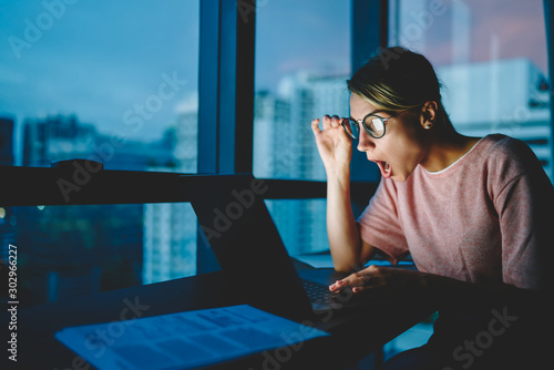 Fototapety, obrazy: Emotional astonished web designer in eyeglasses shocked from last trendy news watching video in network sitting in evening at home. Female shocked with read information in internet receiving news