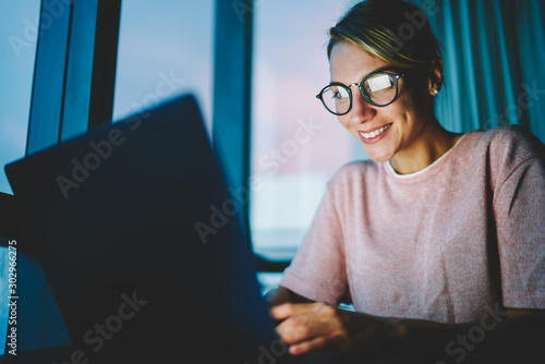 Tela  Young female smiling blogger in spectacles discussing and sharing ideas with followers in personal website on laptop computer