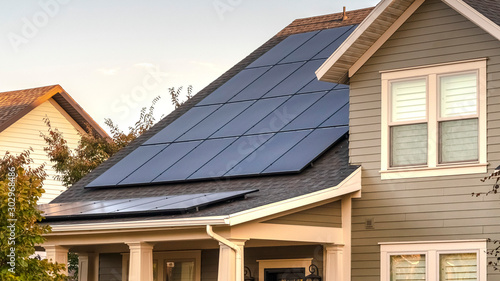 Obraz Panorama frame Solar photovoltaic panels on a house roof - fototapety do salonu