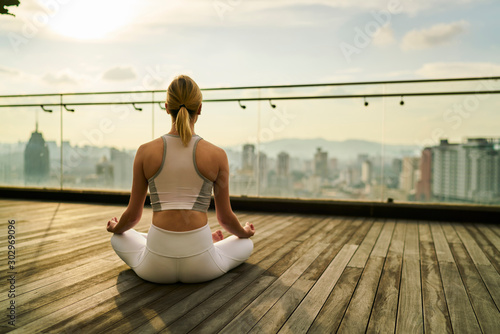 Back view of slim sports women care about body and health in megalopolis training yoga on rooftop of skyscraper, girl in track suit sitting in lotus pose feeling zen in city relaxation concept.