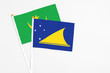 Tokelau and Mauritania stick flags on white background. High quality fabric, miniature national flag. Peaceful global concept.White floor for copy space.