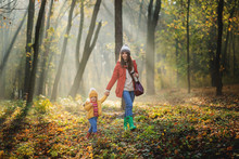 A Young Mother With A Toddler Daughter Walking In Forest In Autumn Nature.