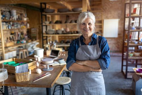 Fotografie, Obraz Portrait of senior female pottery artist in her art studio