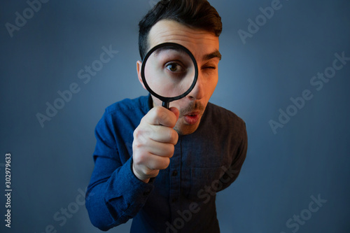 Fotografiet Curious young man with magnifying glass Isolated on grey background