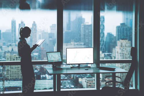 Silhouette of female person hold in hands touch pad while standing near office desktop with Mock up PC computer screen front panoramic city view in window.Trade manager workspace with financial graphs