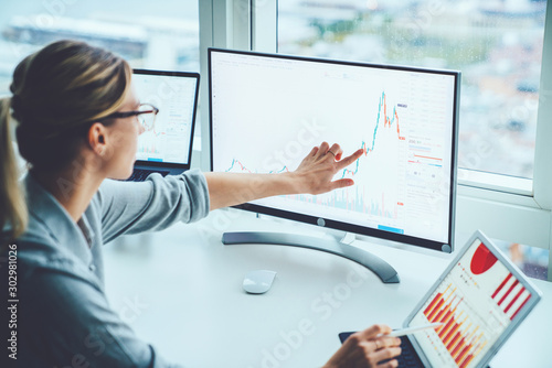 Business woman study financial market to calculate possible risks and profits.Female economist accounting money with statistics graphs pointing on screen of computer at desktop. Quotations on exchange