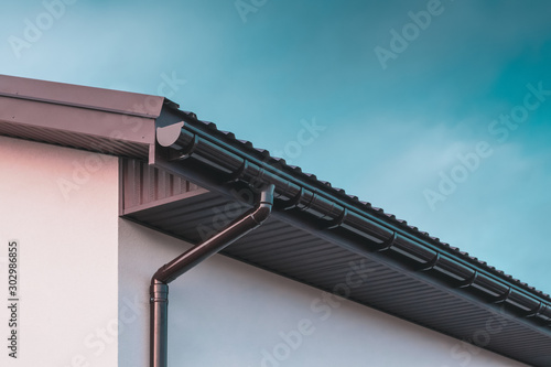 Chocolate-colored plastic gutter on the roof of the building and downpipe on the Fototapete