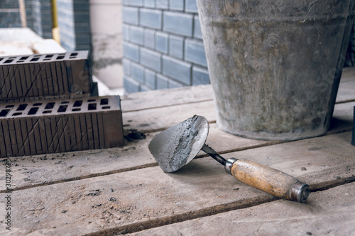 Photo Workplace for a bricklayer close-up. Trowel for bricklaying.