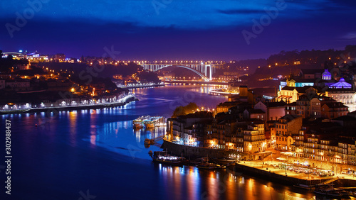 Porto, Portugal. Evening sunset panoramic view at nighttime town. Coastline of river Douro with reflections of illumination in water and picturesque clouds on blue sky.