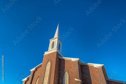 Fotografia Church with classic red brick exterior wall and white steeple against blue sky