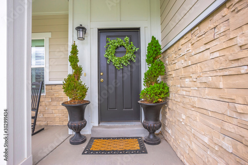 Fotomural  Gray front door of a home with green wreath and flanked by tall potted plants