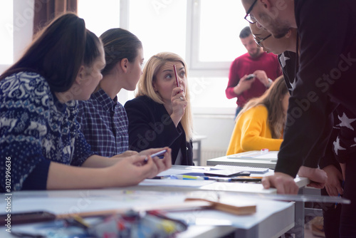 Fototapeta  Beautiful young female teacher helping a student during class