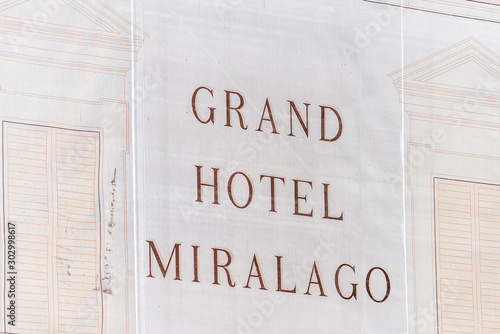 Castiglione del Lago, Italy - August 28, 2018: Medieval town village in Umbria with closeup of sign for Grand Hotel Miralago