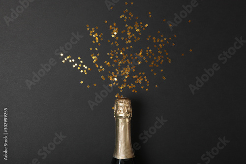 Poster de jardin Alcool bottle of champagne and confetti on a colored background top view. Concept holiday, celebrate, new year, christmas, birthday.