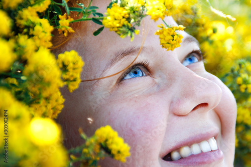 A very close portrait with an emphasis on the amazing blue eyes of a red-haired girl surrounded by bright yellow flowers Canvas-taulu
