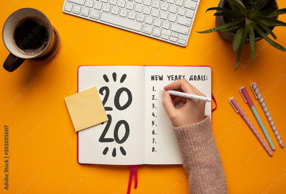 Fototapety, obrazy: Stock photo of a young woman hand writing in a 2020 new year notebook with list of resolutions and objects on yellow background
