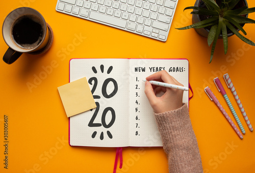 Stock photo of a young woman hand writing in a 2020 new year notebook with list of resolutions and objects on yellow background
