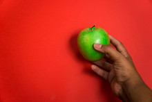 Delicious Green Apple On A Red Background