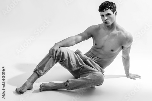 Black and White Muscle strong beautiful stripped male model in denim jeans on white isolated font background with shadow