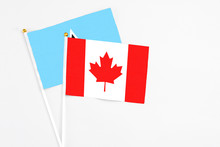 Canada And Saint Lucia Stick Flags On White Background. High Quality Fabric, Miniature National Flag. Peaceful Global Concept.White Floor For Copy Space.