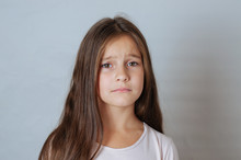 Emotional Portrait Of Strong Emotions Tears Of A Little Beautiful Girl On A White Background