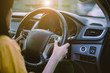 Driver woman hands holding steering wheel and using cruise control on modern car