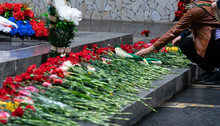 People Offering (laying) The Flowers On The Granite In The Memorial Ceremeny Of Russian Soldiers In Victory Day Of Soviet.