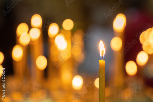 Obraz Candle light in christian church warm tone with dark black background - fototapety do salonu