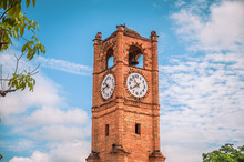 Clock Tower Built Of Brick, In The Background A Blue Sky And Some Green Trees
